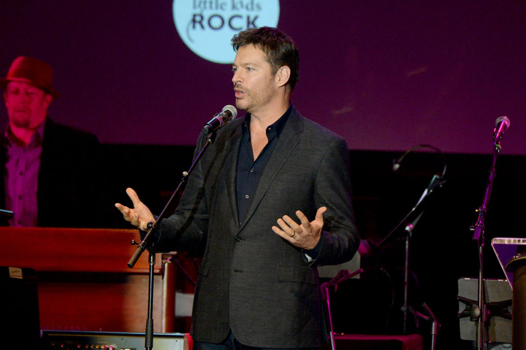 Harry Connick Jr. giving a speech at a Little Kids Rock benefit event onstage.