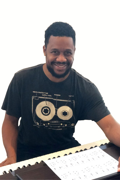 Abasi Aniton is sitting in front of his piano smiling