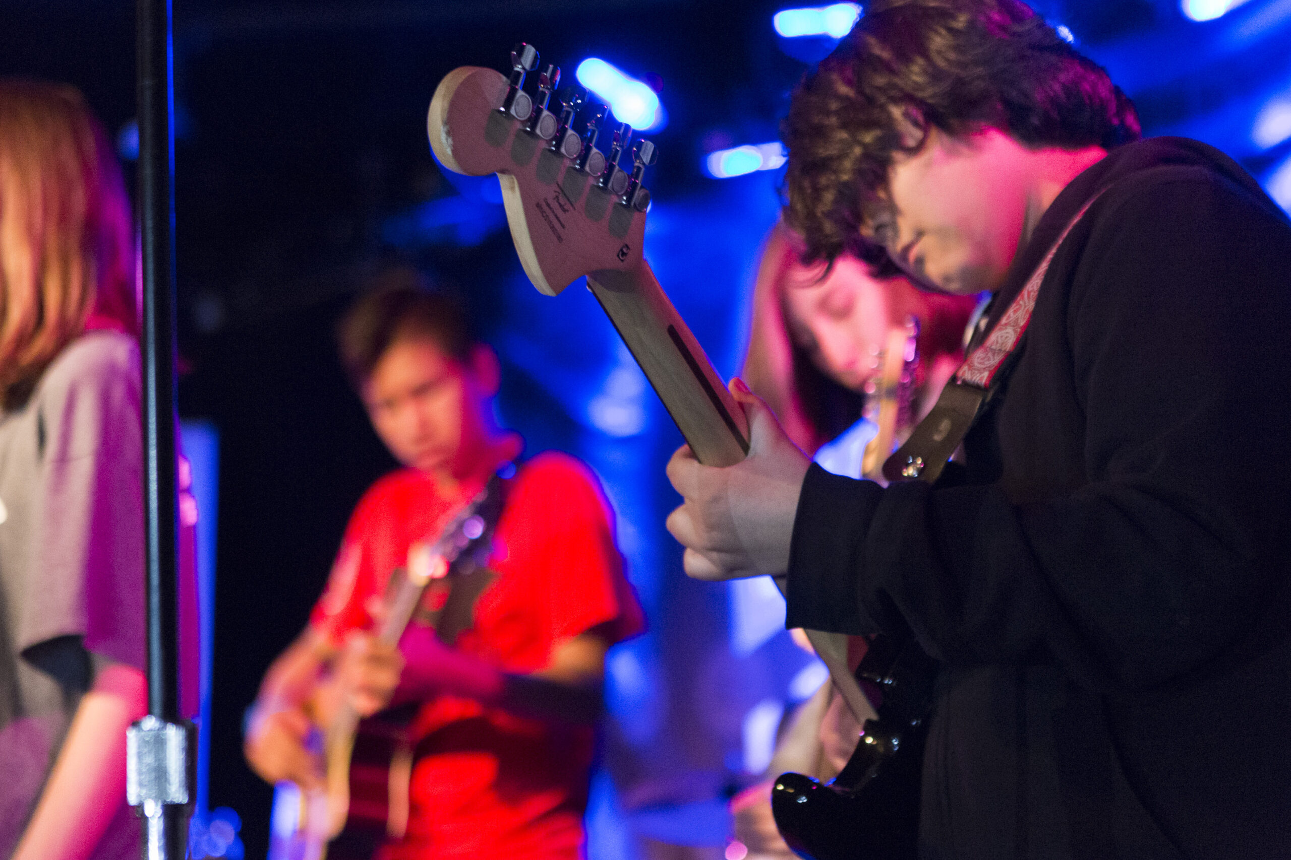 Kid playing electric guitar on stage