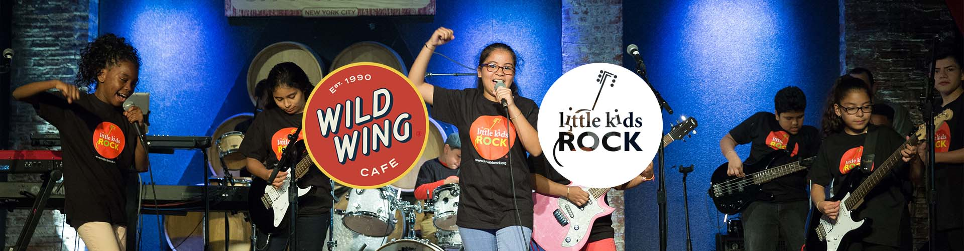 Student band performing onstage with the Wild Wings Cafe and Little Kids Rock logos on top.